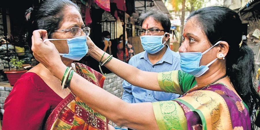 Volunteers distribute face masks at Vashi in Mumbai. (Photo |PTI)