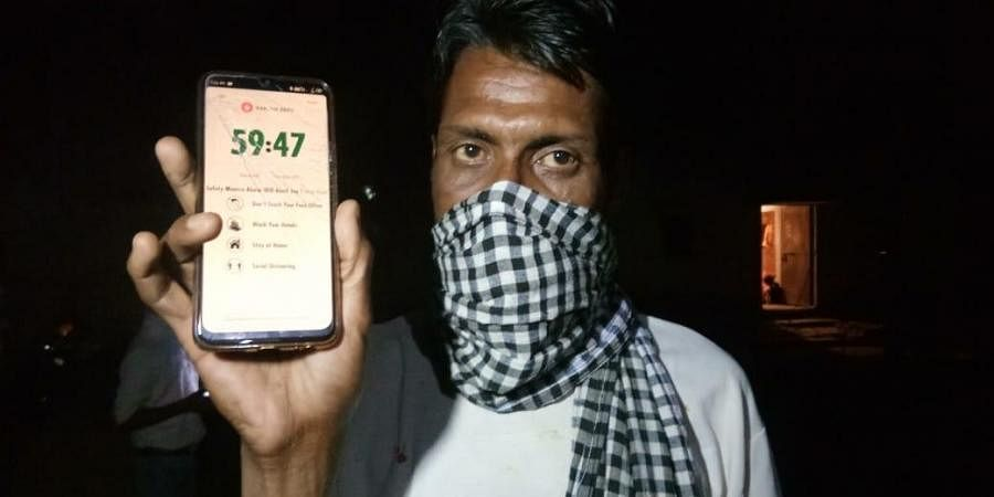 A migrant worker with quarantine app installed on his mobile phone