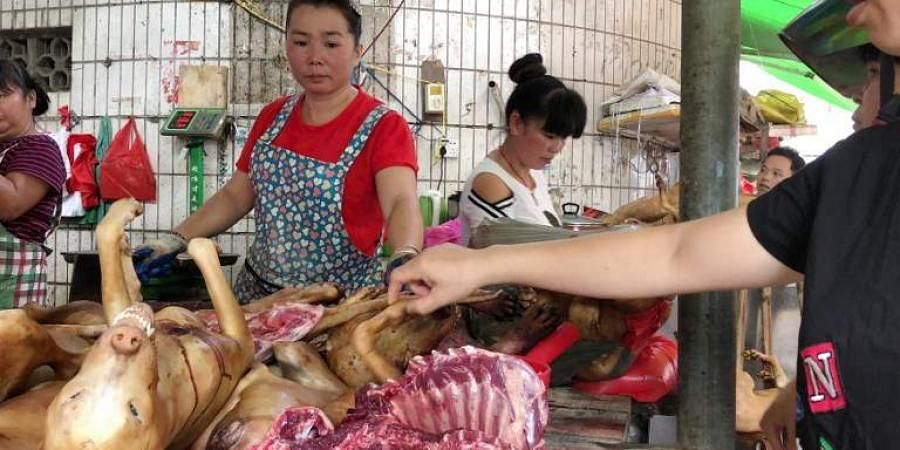 This photo taken on June 20, 2018 shows a customer (R) selecting dog meat at the Dongkou market in Yulin in China.(Photo| AFP)