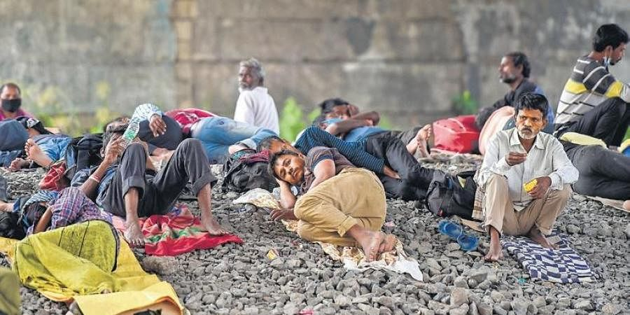 Stranded migrant workers sleep under a flyover next to the railway tracks.