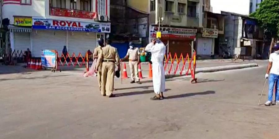 Police personnel stand guard near barricade during the ongoing lockdown to contain coronavirus pandemic, in Vadodara