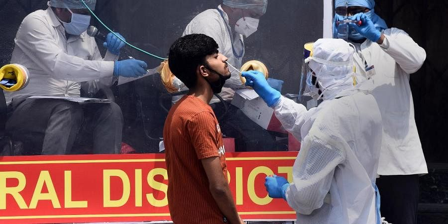 Health workers collect swab samples at a mobile COVID-19 testing van at Delhi's Filmistan area on Friday
