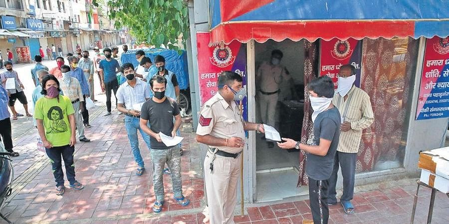 Delhi Police personnel check documents of migrant labourers before their registration to return home