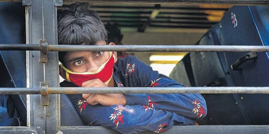 A migrant longing to reach his native place, looks through the window of a bus in Kolkata on Wednesday.