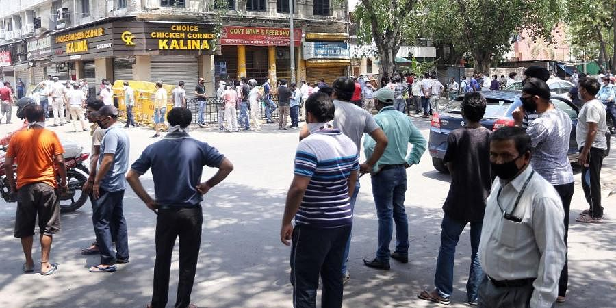People stand in the queue to buy liquor outside liquor shop at Gole Market after the government eased a nationwide lockdown imposed as a preventive measure against the spread of the COVID-19 coronavirus, in New Delhi