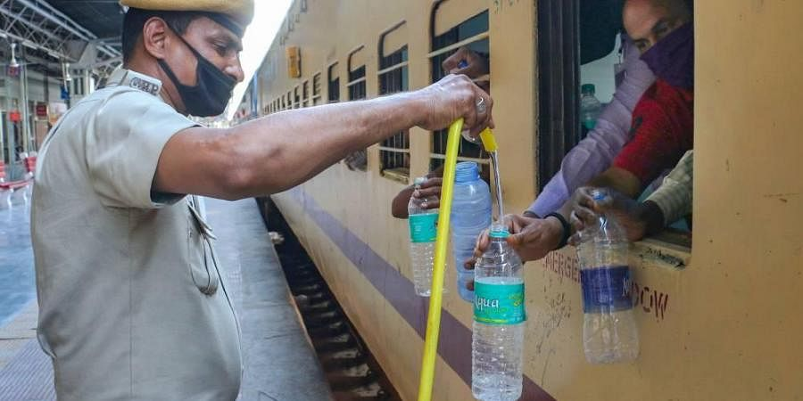 A policeman provides drinking water to a migrant before leaving towards Bihar in a train during the ongoing COVID-19 nationwide lockdown in Ajmer Sunday