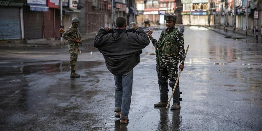 A paramilitary soldier orders a Kashmiri to open his jacket before frisking him during curfew in Srinagar.