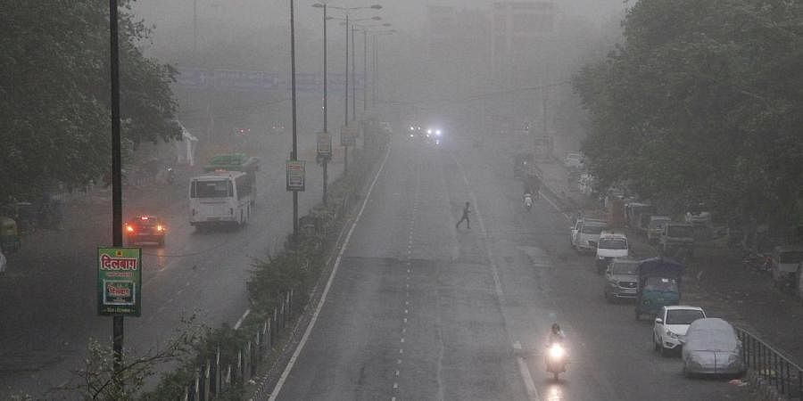 Vehicles passing through rain and duststorm in Delhi on Sunday