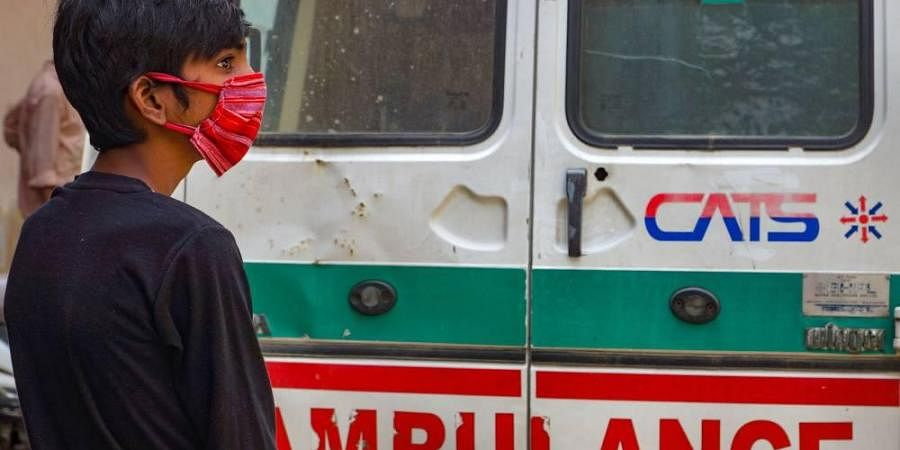 A suspected COVID-19 patient wearing a mask stands near an ambulance before being taken to a hospital for quarantine at Kalyanpuri area during the nationwide lockdown in East Delhi