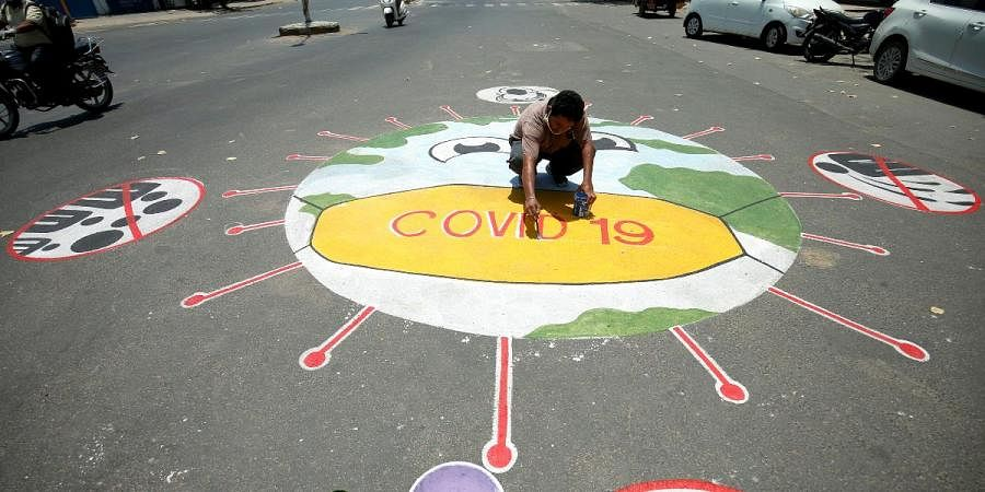 A man draws a message on a road to raise awareness about the spreading of coronavirus disease in Ahmedabad