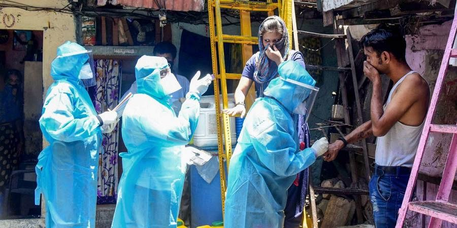 Health workers wearing protective suits screen resident of Kumbharwada during a house-to-house health survey at Mumbai's Dharavi