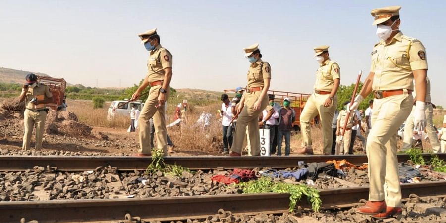 Police personnel inspect the spot after a goods train ran over a group of migrant workers while they were sleeping on the tracks, in Aurangabad