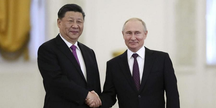 Russian President Vladimir Putin (R) and Chinese President Xi Jinping shake hands during their meeting in the Kremlin in Moscow
