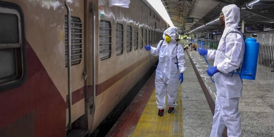 Workers sanitise a train coach at Guwahati Railway Station during the ongoing COVID-19 nationwide lockdown in Guwahati