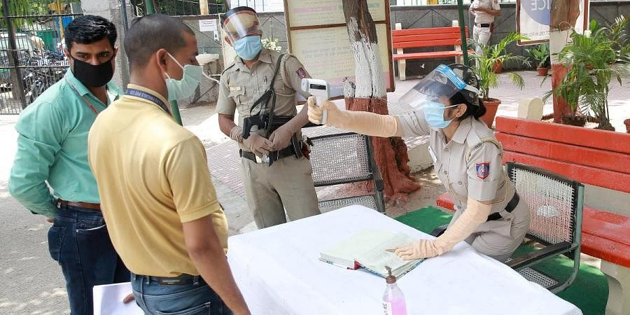A man undergoes temperature test as he arrves at RK Puram Police Station amid ongoing COVID-19 lockdown in New Delhi