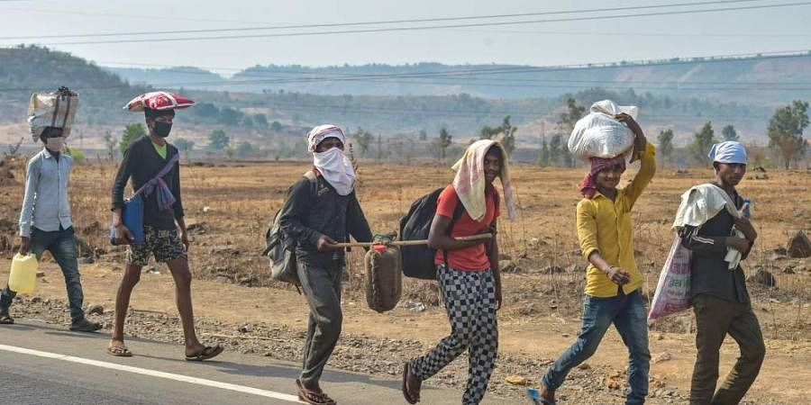 Migrants with their belongings walk towards their native places on the Mumbai-Nashik highway during the nationwide lockdown in wake of the coronavirus pandemic in Thane