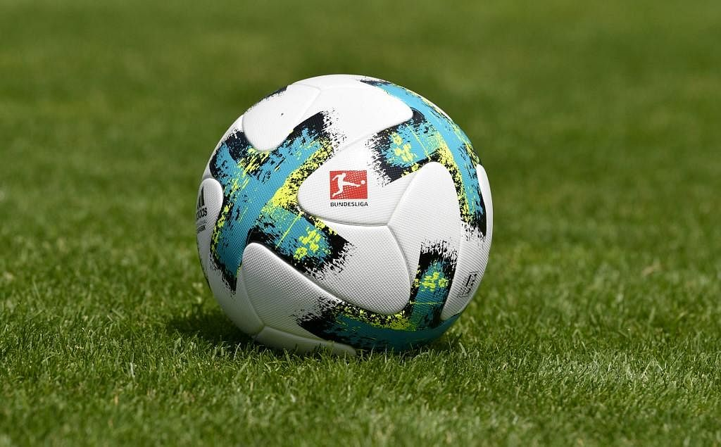 A ball with the logo of the German first division football league Bundesliga is seen on the pitch. (Photo | AFP)
