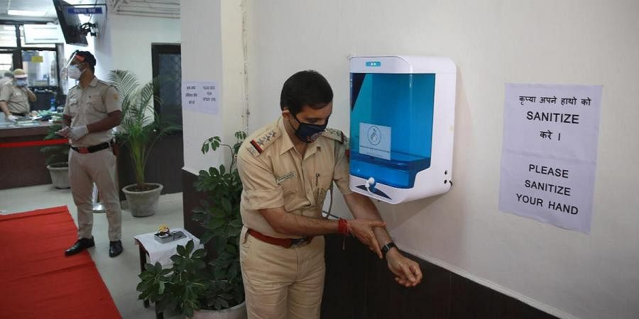 A police man sanitizes his hands with a sanitiser dispensing machine installed at RK Puram Police Station amid the COVID-19 lockdown in New Delhi