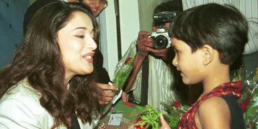 Bollywood actress Madhuri Dixit giving a rose to a cancer patient on Rose Day at Hinduja Hospital.