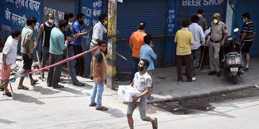 A customer carries alcohol after purchasing from a wine shop during the ongoing COVID-19 nationwide lockdown at Vishwas Nagar in East Delhi
