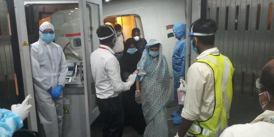 Passengers exit an AI repatriation flight.