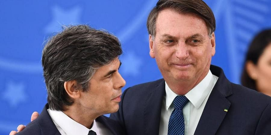 Brazilian President Jair Bolsonaro, right, embraces Nelson Teich after his appointment as health minister on April 17, 2020.