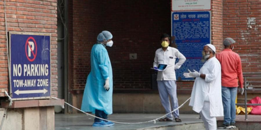A healthcare worker of LNJP in a PPE kit interacts with people