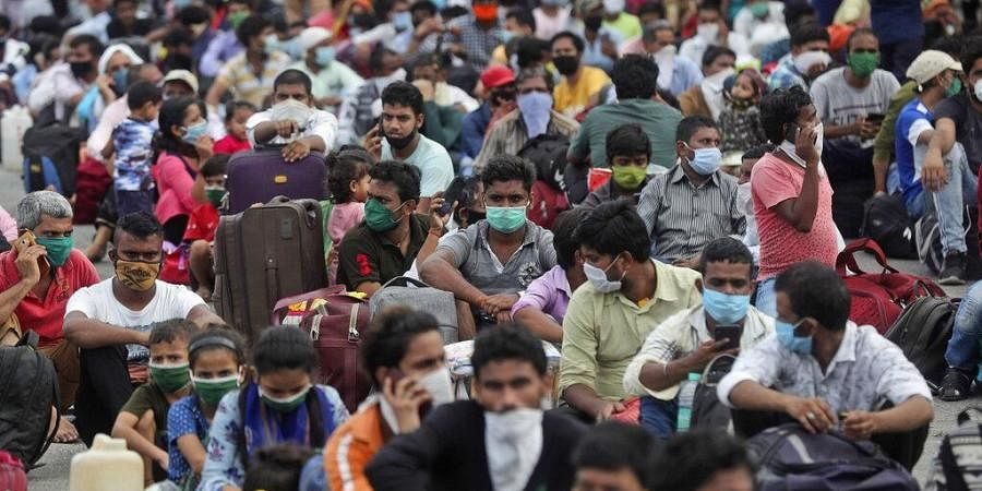 Migrant workers from other states wait outside a railway station to catch a train to return to their homes, in Mumbai, India, Friday, May 15, 2020.