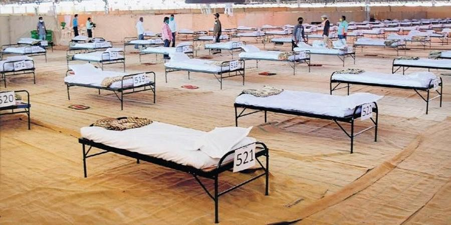 Workers set up beds at a coronavirus care centre of Nagpur Municipal Corporation.