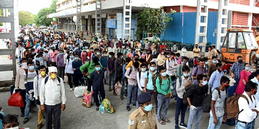 Stranded migrant laborers queue to board a special train to Rewa (Madhya Pradesh) from MGR Central railway station after the government eased a nationwide lockdown imposed as a preventive measure against the COVID-19 coronavirus, in Chennai