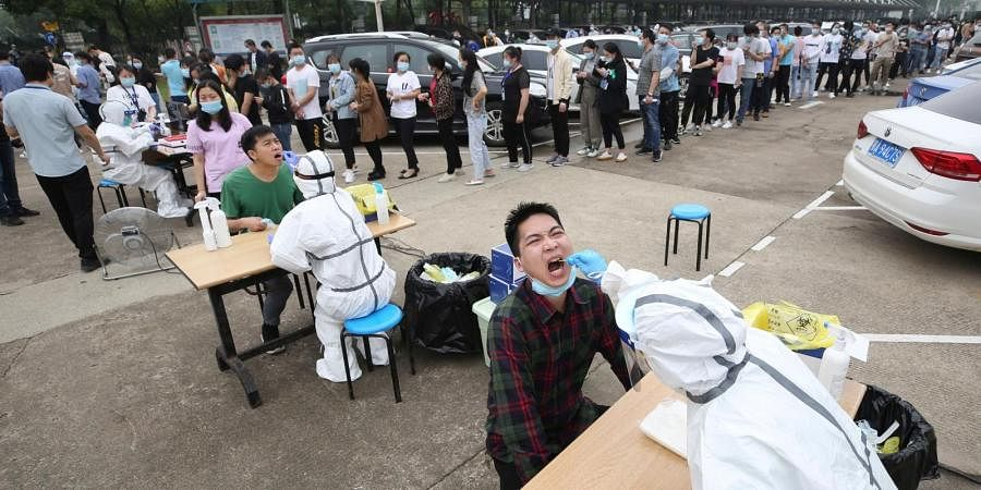 Workers line up for medical workers to take swabs for the coronavirus test at a large factory in Wuhan