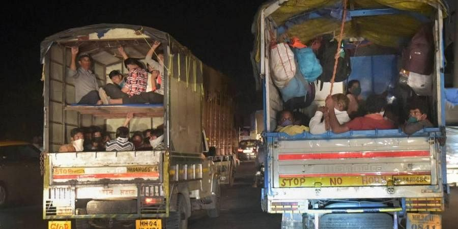 Migrants from northern states ride cargo vehicles on Mumbai-Nashik highway to reach their native places during the ongoing COVID-19 lockdown in Thane late night on Friday