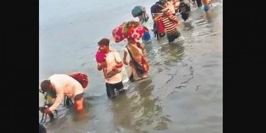 A still from a video showing migrants crossing the Yamuna