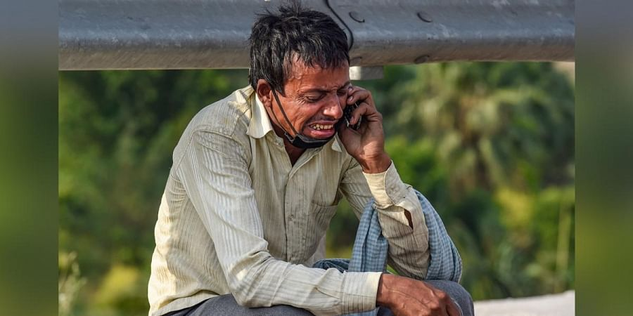 A migrant labourer reacts while talking to a relative over his mobile phone, at Nizamuddin Bridge in New Delhi, Monday, May 11, 2020, during ongoing COVID-19 lockdown