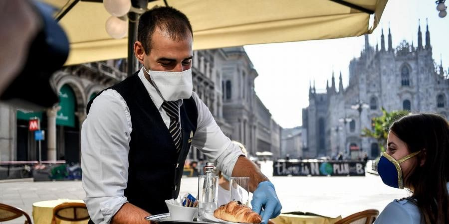 Two girls have breakfast served at a bar in front of the gothic Cathedral in Milan, Italy