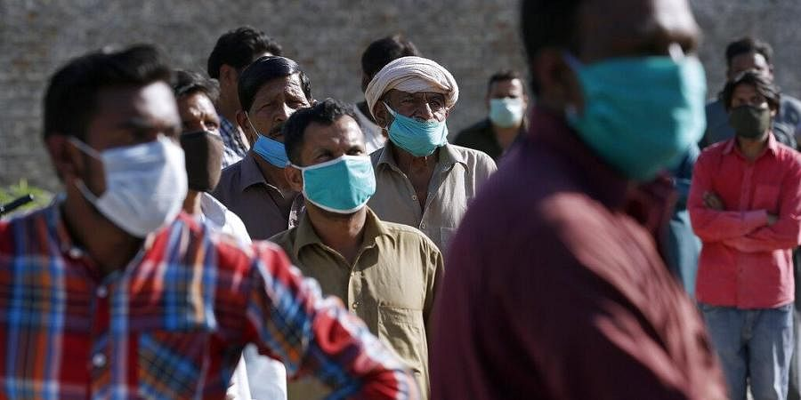People wearing protective mask wait their turn to receive free sacks of wheat flour and other food supplies provided by a charity group Act of Kindness Pakistan