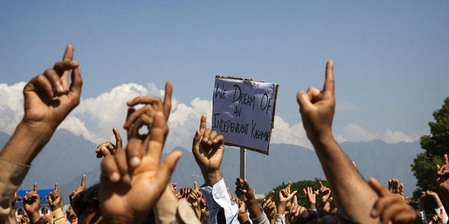 Kashmiri men shout freedom slogans during a protest against New Delhi's tightened grip on the disputed region, after Friday prayers on the outskirts of Srinagar.
