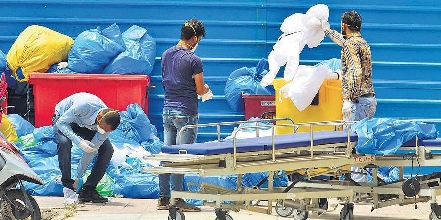 Health workers dispose of medical waste in open at a government hospital in New Delhi
