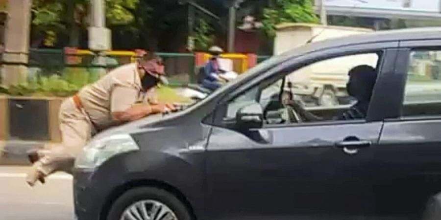 A car driver drags a police officer on car's bonnet in Jalandhar, after the officer tried to stop the vehicle