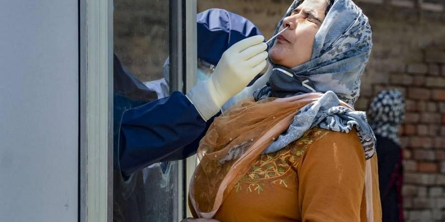 A medic collects samples from a woman for COVID-19 tests at a 'red zone' during a nationwide lockdown to curb the spread of coronavirus in Srinagar Tuesday