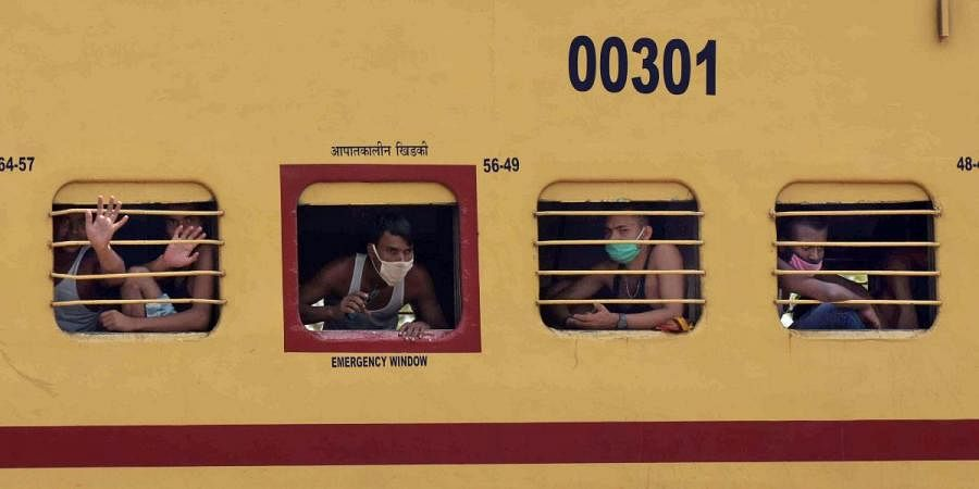 Migrant workers see outside the train window as they travel in a special train to arrive in their native places during a government-imposed nationwide lockdown as a preventive measure against coronavirus, in Prayagraj on Monday