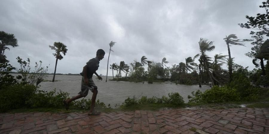 A boy runs along an embankment ahead of the expected landfall of cyclone Amphan, in Dacope