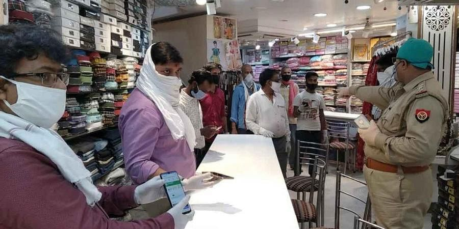 A police official asking people to maintain social distance and use Arogya Setu app at a store in Varanasi