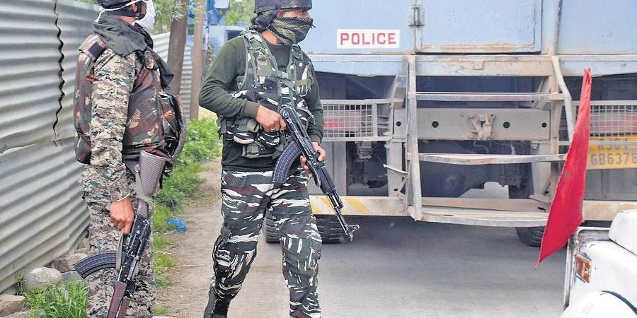 Security personnel take cover as forces engage with Hizbul terrorists at Awantipora in south Kashmir on Wednesday