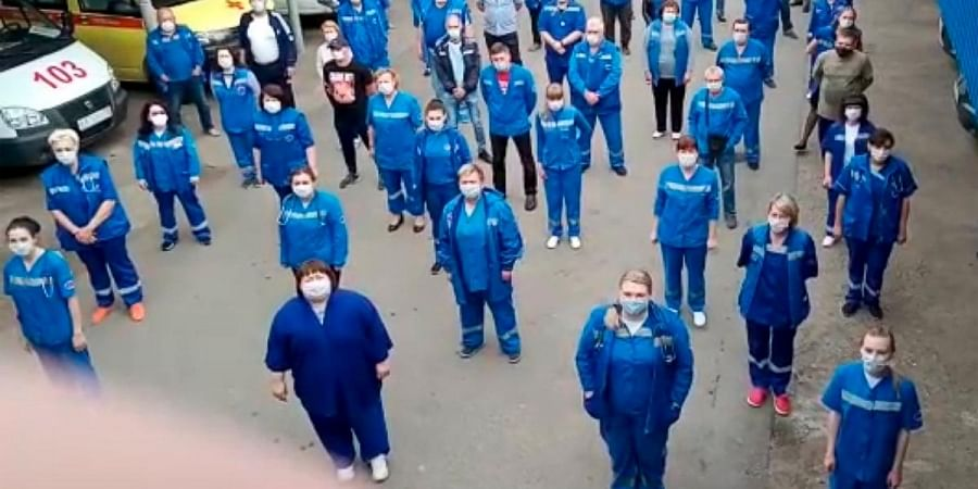 In this handout photo taken from video footage, medical workers record s video appeal to Russian President Vladimir Putin in Armavir, Russia, Saturday, May 16, 2020.