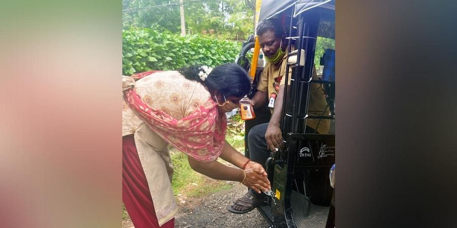 Suresh Kumar M opens the tap for a customer to wash her hands