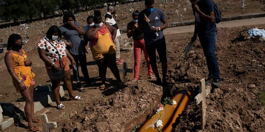 Relatives attend the burial of Vandelma Rosa de Almeida, 66, whose death certificate states is suspected of having died of COVID-19, at the Caju cemetery in Rio de Janeiro, Brazil, Wednesday, May 20, 2020.