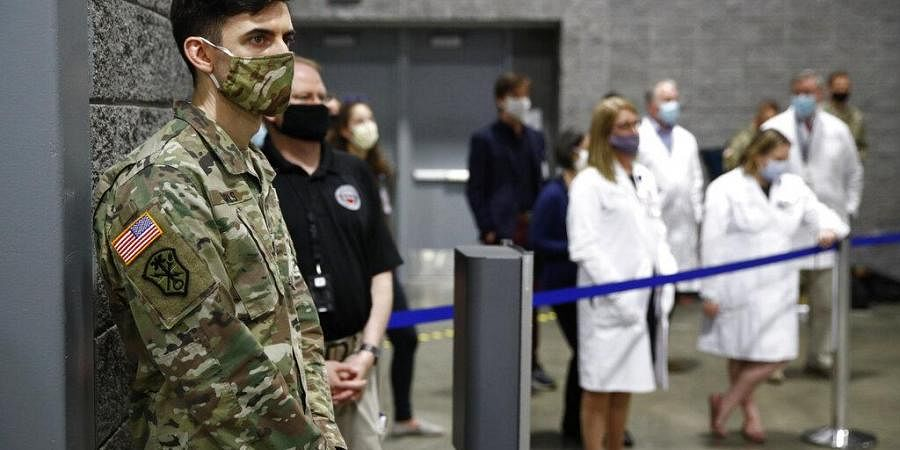 A member of the U.S. Army and medical professionals practice social distancing as they attend a news conference with District of Columbia Mayor Muriel Bowser at a temporary alternate care site constructed in response to the coronavirus outbreak inside the Walter E. Washington Convention Center