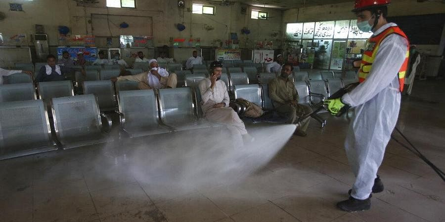 A health worker disinfects a bus terminal that reopened after the government relaxed the weeks-long lockdown that was enforced to curb the spread of the coronavirus, in Peshawar, Pakistan