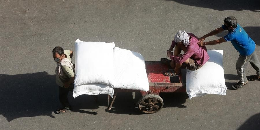 Labourers push a loaded cart in Khari Baoli after lockdown restrictions were eased in New Delhi, on Thursday